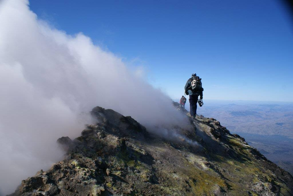 Científicos del INVOLCAN realizando medidas de emisión de gases en el borde del cráter principal del volcán Etna, Italia.